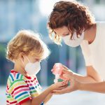 Child and Adult Wear Masks and Use Hand Sanitizer
