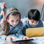 sister and brother using tablets