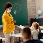 teacher and students wearing protective face masks in the classroom