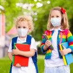 Two children wearing masks ready for school