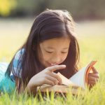 girl lying in grass reading book on sunny day