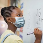 schoolgirl solving addition problem on white board during Covid-19 pandemic